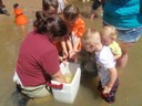 Mussel outreach event in which children are assisting a biologist to release host fish that were recently infested with mussel larvae.